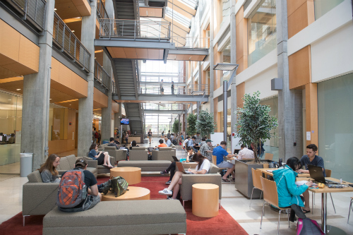 Students gathered inside lobby of building working