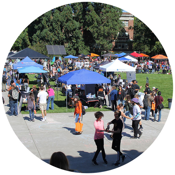 a wide shot of many people and booths on the quad
