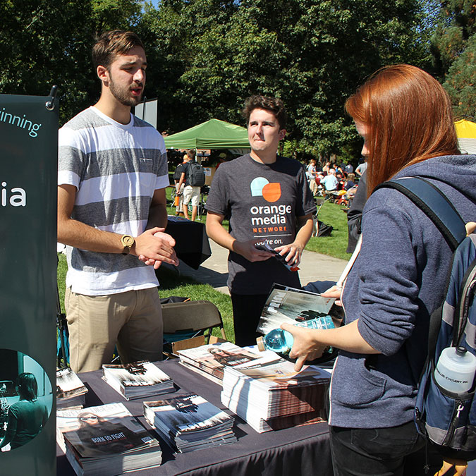 students at a booth advertising orange media network