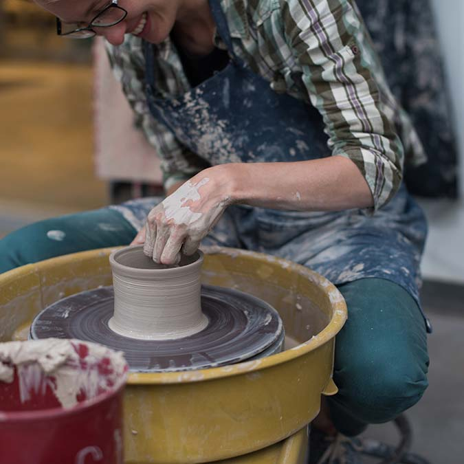 woman creating sculpture on a pottery wheel