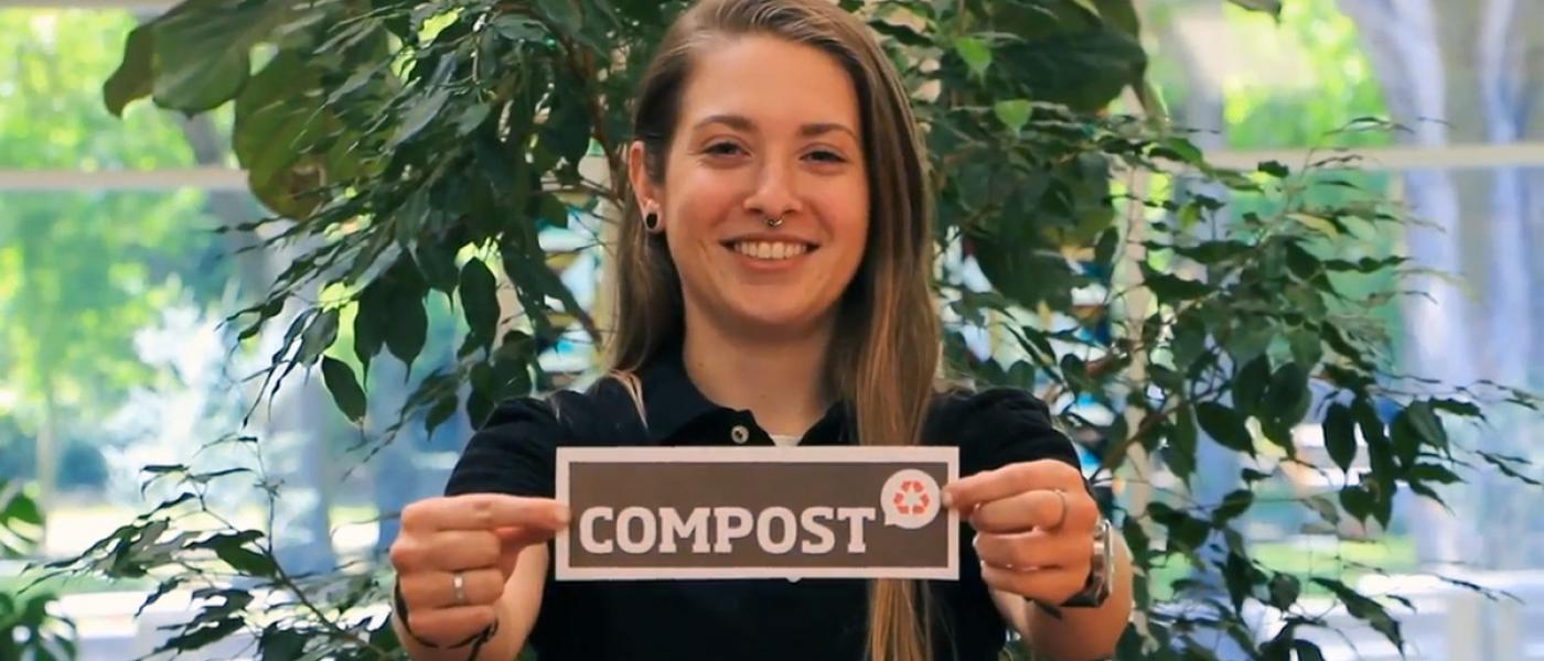 """Alyssa Lillybridge smiling and holding sign that says """"COMPOST"""""""