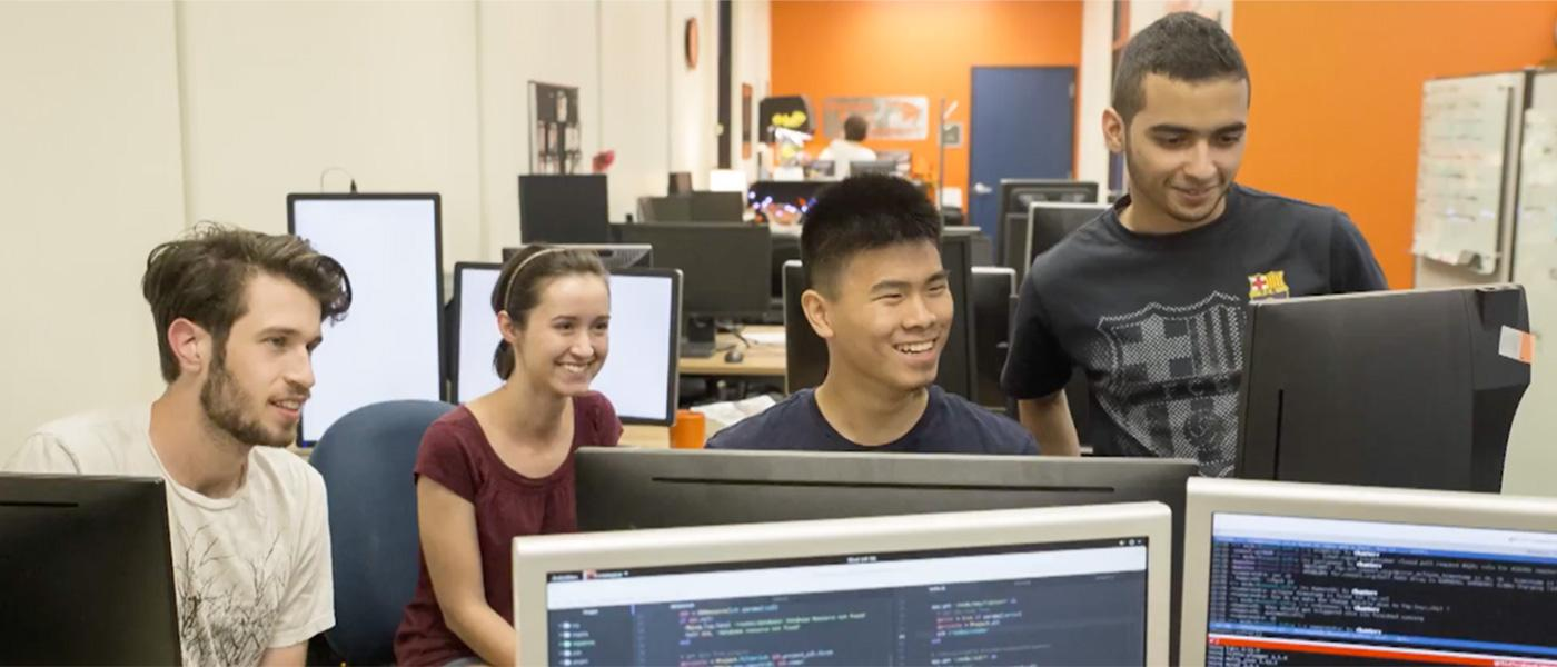Four students in front of a computer working together