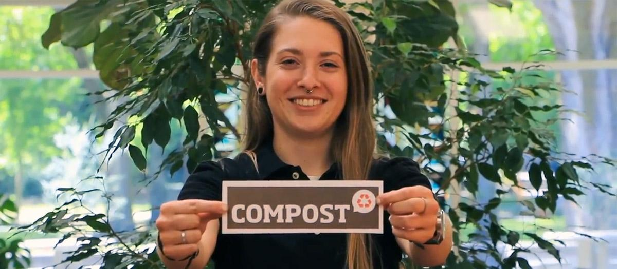 "Alyssa Lillybridge smiling and holding sign that says ""COMPOST"""